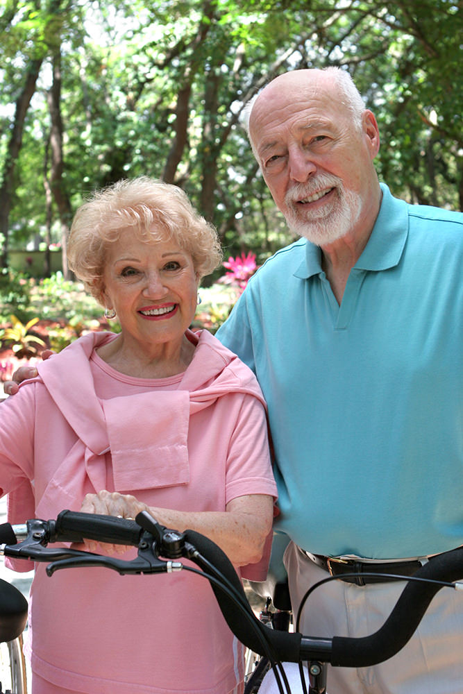 A happy, active senior couple going for a bike ride.