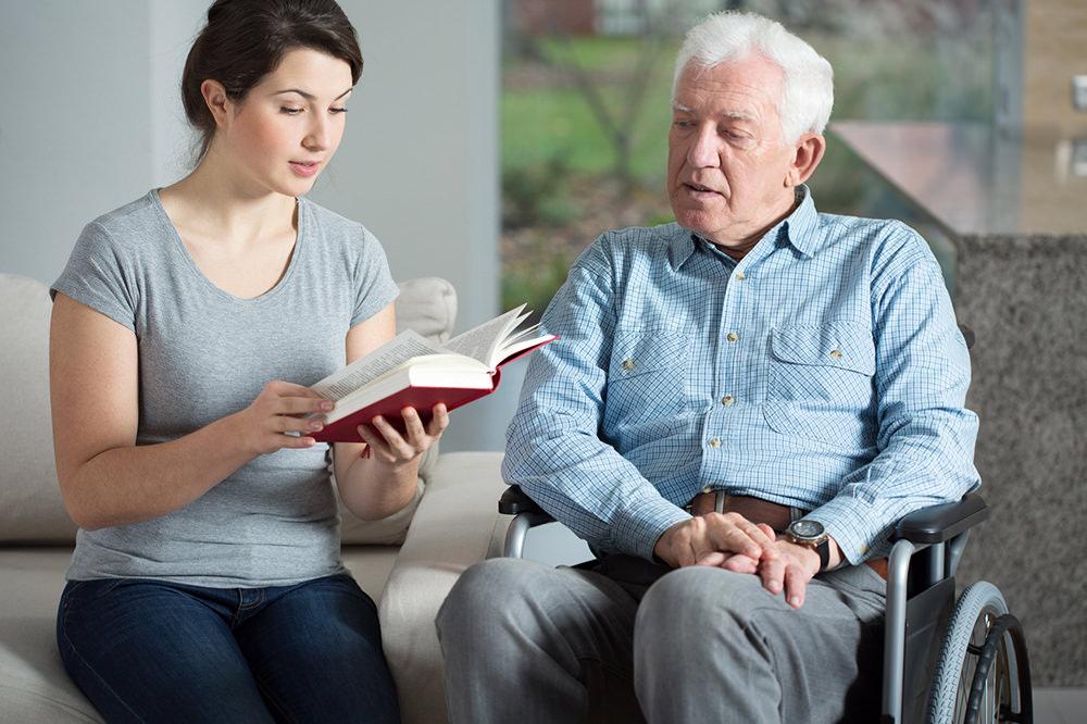 Senior care assistant reading book elderly man