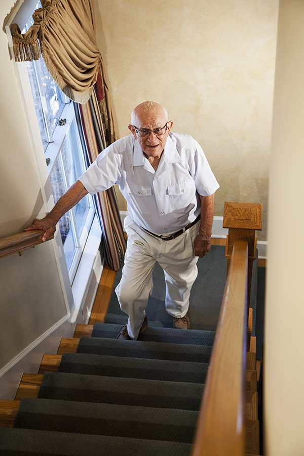 Senior man (80s) climbing staircase.