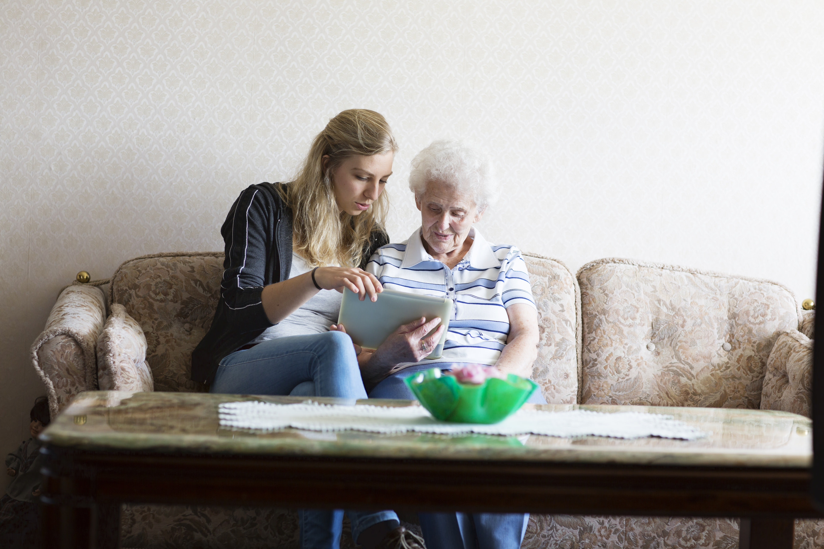 caregiver and senior woman, 90 years old, sitting on sofa, and looking at tablet pc