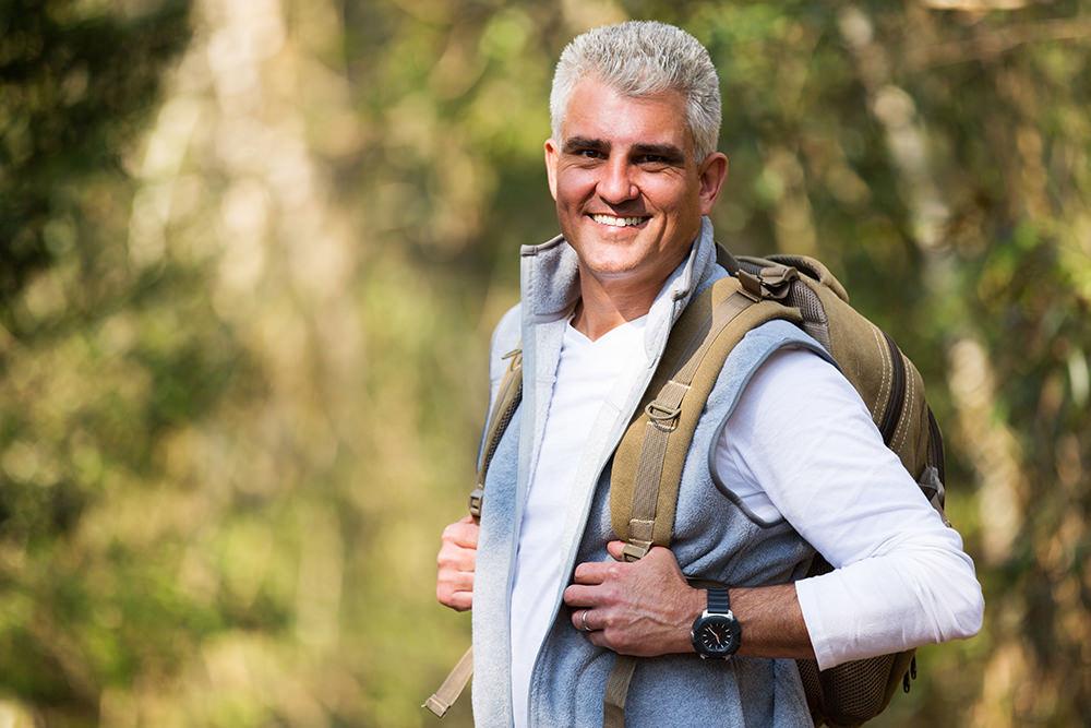 happy senior man on hike looking at the camera